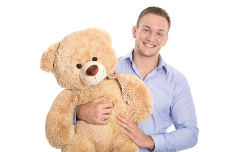 solo  christmas: Isolated smiling happy and attractive young man holding teddy bear in his hands.