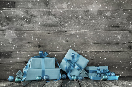 Grey wooden christmas background with a stack of festive wrapped presents in blue or turquoise.