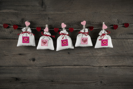 Presents with hearts hanging on wooden background for birthday, christening, valentine or christmas. photo