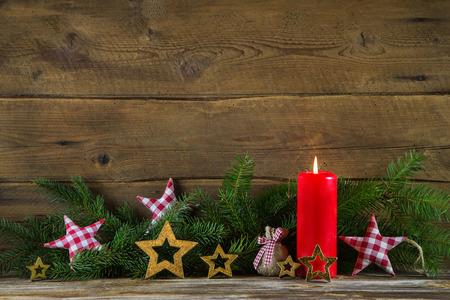 corona de adviento: La decoración de Navidad Clásica: vela roja y ramales en fondo de madera vieja.