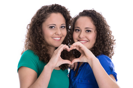 two women hugging: Happy young girls making heart with hands: real twin sisters isolated over white.