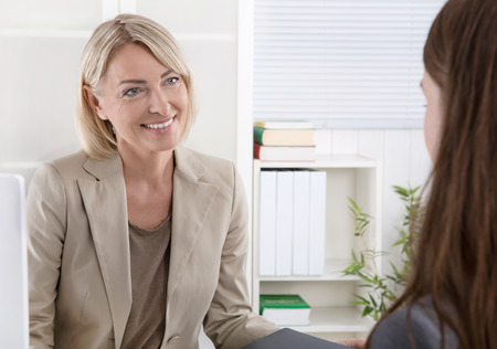 discussions: Mature businesswoman in a job interview with a young woman. Stock Photo