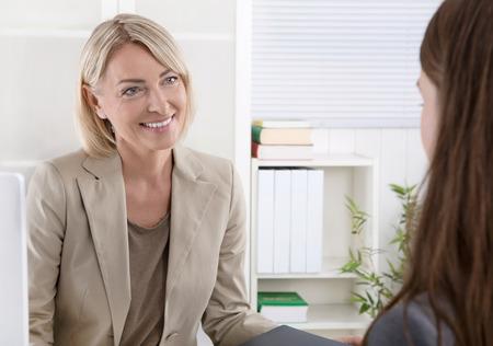 personas hablando: Pareja de negocios en una entrevista de trabajo con una mujer joven. Foto de archivo