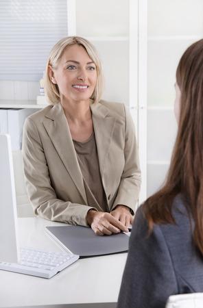 Fällige Geschäftsfrau in einem Vorstellungsgespräch mit einer jungen Frau.