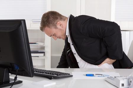L'homme d'affaires assis à son bureau à avoir des douleurs au dos, les reins ou les muscles.