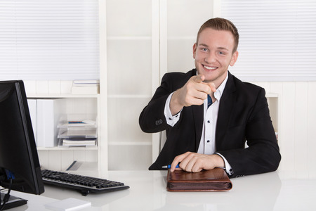 finger tip: Happy young business man sitting in his office give advice for customers.