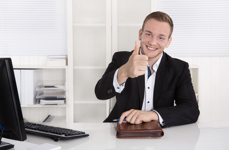 Heureux jeune homme d'affaires assis dans son bureau décision pouce geste et de recommander un produit. Banque d'images