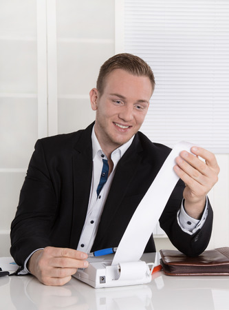 Happy entrepreneur looking at paper roll: concept for increasing income and a good balance sheet. Stock Photo