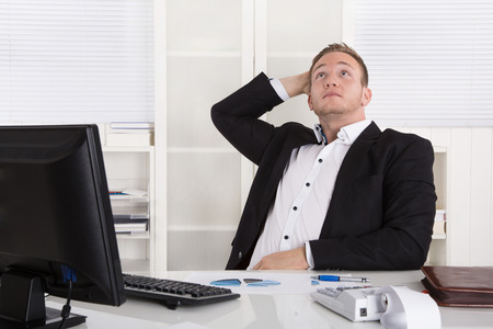 Pensive young dreaming businessman sitting at desk looking up at ceiling. photo