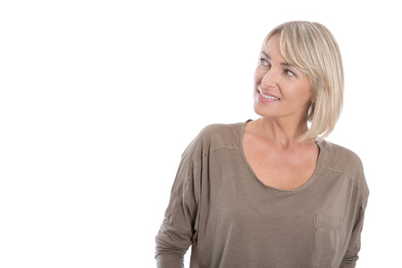 Attractive mature blond smiling woman looking sideways to text.