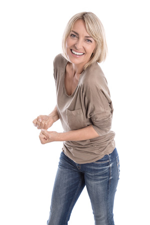likable: Cheering happy older isolated blond woman in blue jeans and white teeth. Stock Photo
