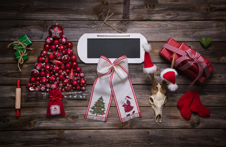 good wishes: Wooden christmas background with red decoration and an empty sign or card for good wishes. Stock Photo