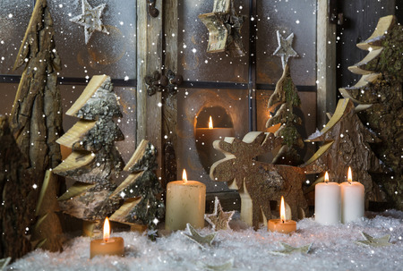 Handmade christmas decoration with wooden trees and reindeer decorated in the window. photo