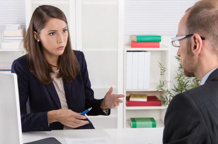 entrevista: Cliente y sonriendo agente financiero de la mujer en una discusi�n en el escritorio. Foto de archivo