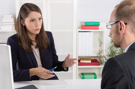 customer: Customer and smiling female financial agent in a discussion at desk. Stock Photo