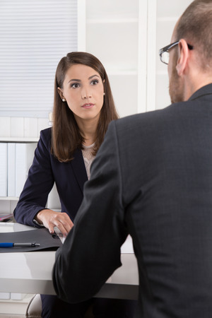 Customer and smiling female financial agent in a discussion at desk. Imagens - 33070488