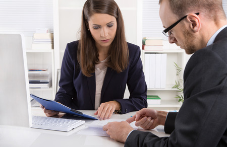 executive: Customer and smiling female financial agent in a discussion at desk. Stock Photo