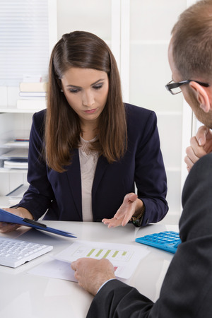 career counseling: Customer and smiling female financial agent in a discussion at desk. Stock Photo