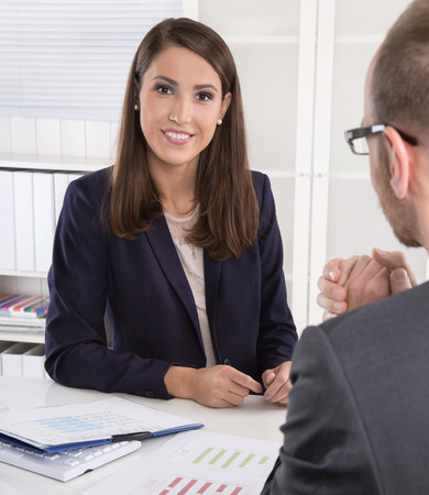 Customer and smiling female financial agent in a discussion at desk. Zdjęcie Seryjne