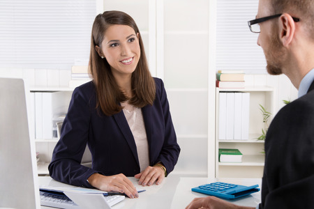 sales bank: Customer and smiling female financial agent in a discussion at desk. Stock Photo