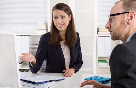 Customer and smiling female financial agent in a discussion at desk. Foto de archivo