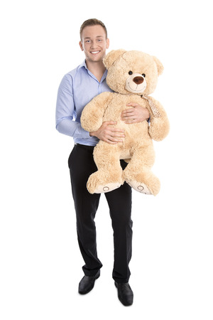 solo  christmas: Happy young man holding a teddy bear in his hands getting soon a baby.