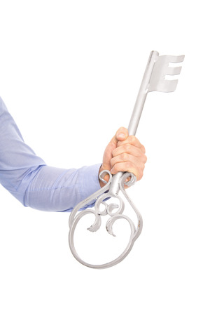 Isolated businessman holding a silver key in his hand wearing blue shirt. photo