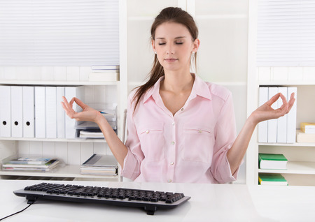 office force: Young business woman making a break in the office and meditate. Stock Photo