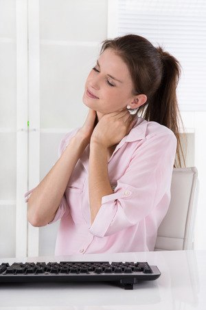 swollen: Young woman sitting in the office having ache in the neck or swollen lymph nodes, Stock Photo