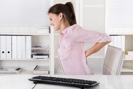 fisico: Mujer joven en la blusa rosa sentado con dolor de espalda en la oficina.