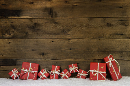 Wooden rustic country background with red christmas presents. Stock Photo