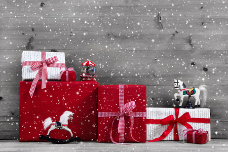 copy christmas: Red Christmas presents and gift boxes with horse on grey wooden background