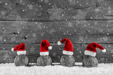 Grey festive wooden christmas background with four santa hats on xmas balls.