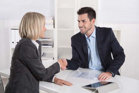 sales agent: Successful business meeting with handshake: customer and client shaking hands in the office.