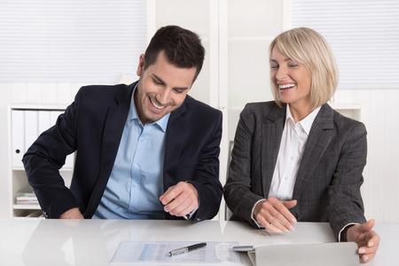 humorously: Smiling business team having fun in the office: daily hustle concept with man and woman.