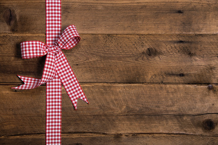 Wooden rustic background with a red white checked ribbon. Surface for a christmas present or gift certificate. Standard-Bild