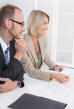 committee: Successful business team of man to woman sitting around a table talking together.