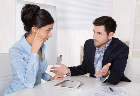workplace: Conflict and problems on workplace: discussing boss and trainee in a meeting. Stock Photo