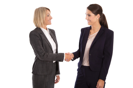 Team: Two smiling isolated business woman shaking hands wearing business outfit