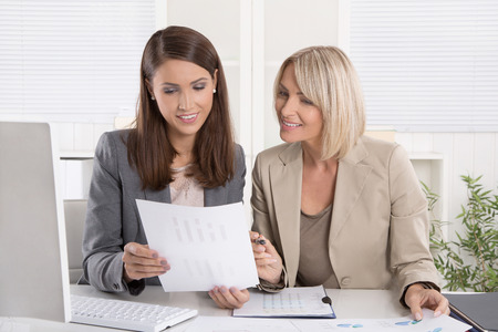 Female senior and junior consultants sitting at desk working together in a business team.