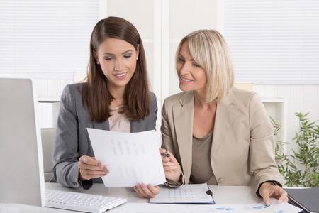 papeles oficina: Mujeres consultores senior y junior sentado en el escritorio de trabajo en equipo de negocios.