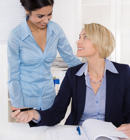 Friendly atmosphere at work: two smiling business woman in the office. photo