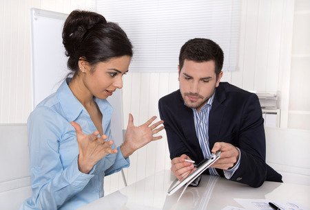 outgoings: Stunned business woman in blue with her boss looking at tablet screen. Stock Photo