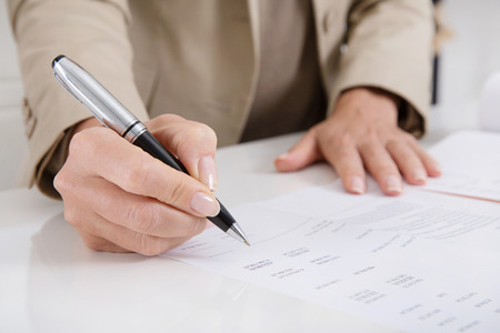 outgoings: Female controller analyzing costs and revenue with a pen and control management assessment numbers. Stock Photo