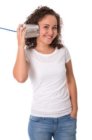 humorously: Funny natural young happy girl listening on tin can phone.