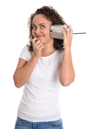 tin can phone: Funny natural young happy girl listening on tin can phone.