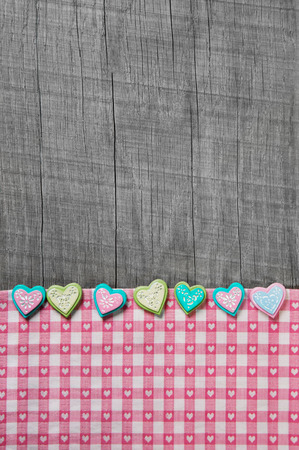 marriage certificate: Shabby chic grey wooden background with hearts on a pink white checkered frame.