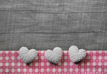 shabby chic background: Greeting card: three white and pink checked hearts on wooden grey shabby chic background or wedding, birthday or valentines day.