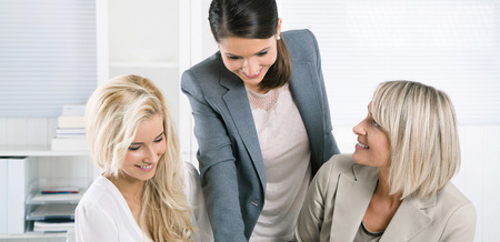 advisers: Successful team of smiling businesswoman sitting at desk wearing business outfit.