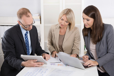 Team of three business people sitting together at desk in a meeting or discussion. Stock Photo
